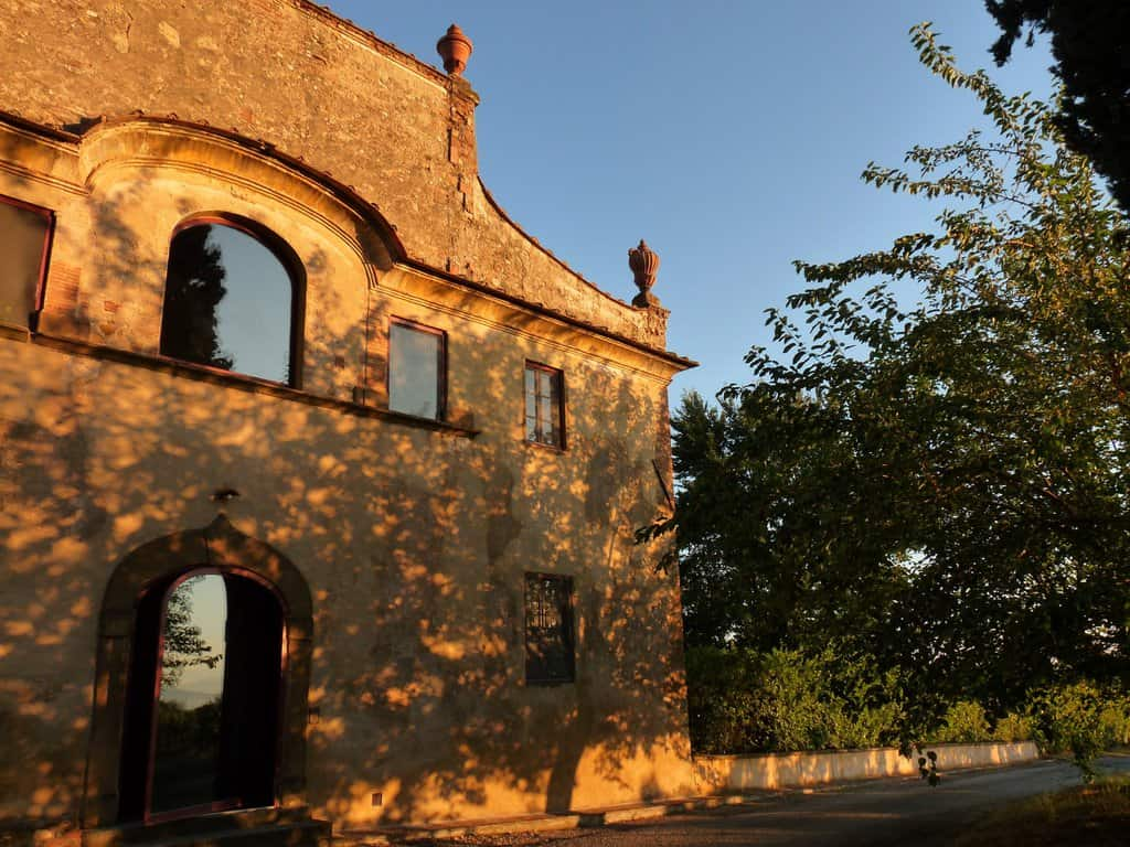 Sun on yellow stone facade of Tuscan villa.