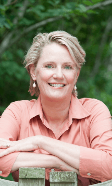 Portrait of Author Kathryn Kay in an orange shirt