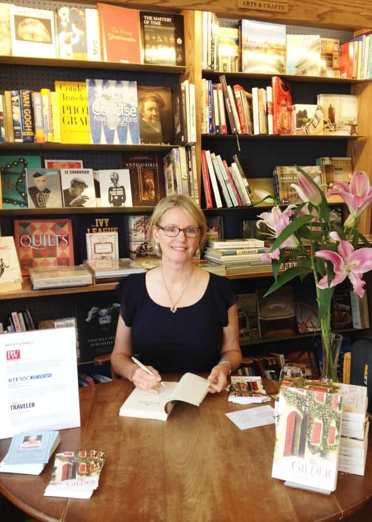 Author Kathryn Kay sits a table with a book in her hand and bookshelves in the background.