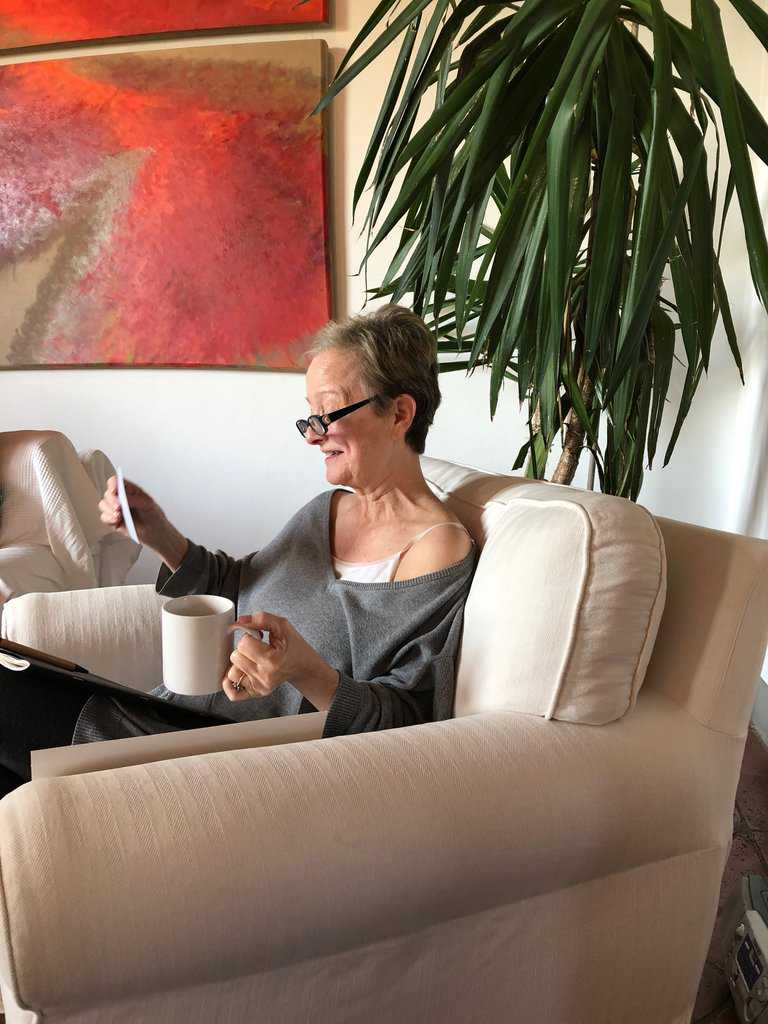 A woman writer sitting in an armchair reads her writing aloud