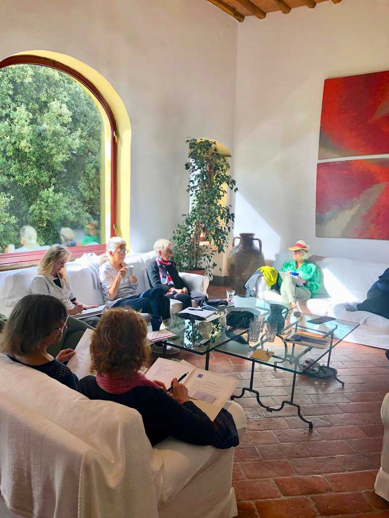 6 women writers sit in living room writing at A Writer Within retreat in Tuscany, Italy
