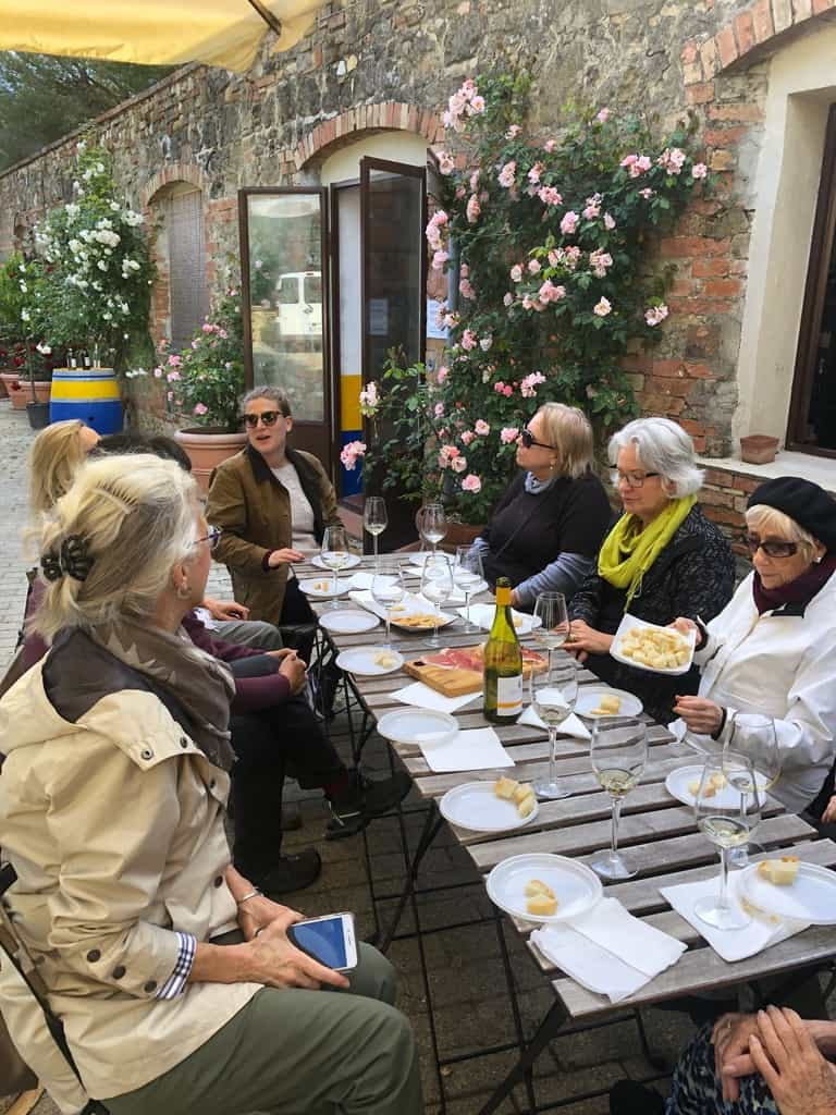 7 women writers sit at a winery table for wine tasting on an outing with A Writer Within in Tuscany, Italy