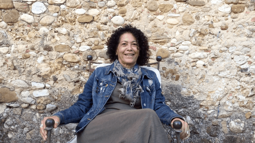 Author Lisa Ramee sits in front of stone wall at A Writer Within retreat in Tuscany, Italy