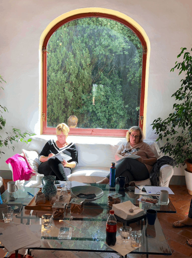 Two women sit on a coach writing in front of a large window at A Writer Within's Tuscany retreat