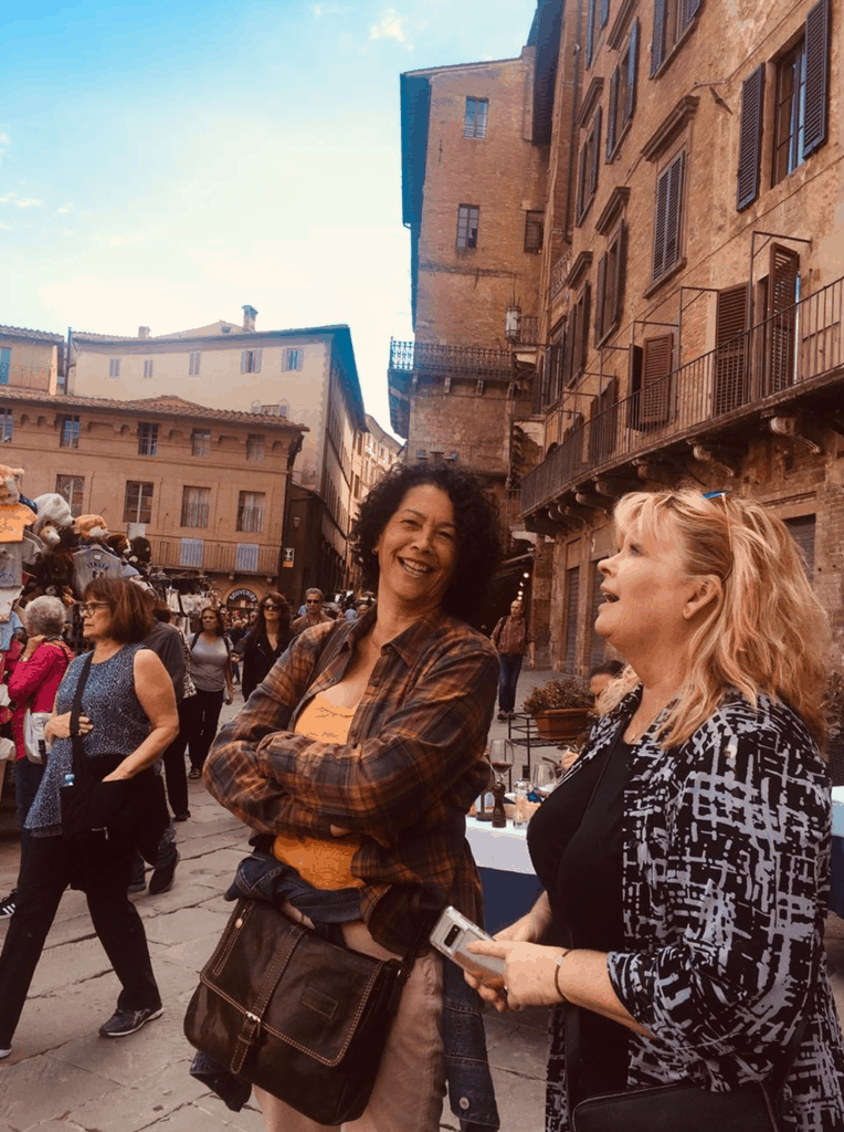 Two women chatting and smiling while on A Writer Within's Tuscany Writing Retreat