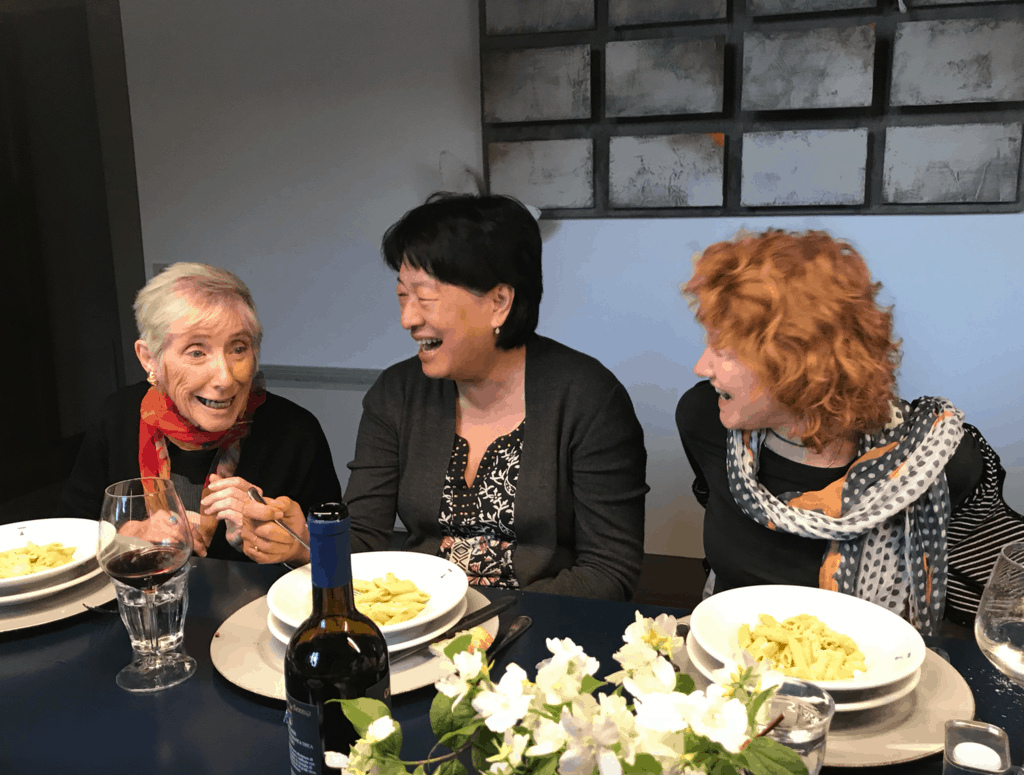 3 women writers laughing at dinner table at A Writer Within's retreat in Italy